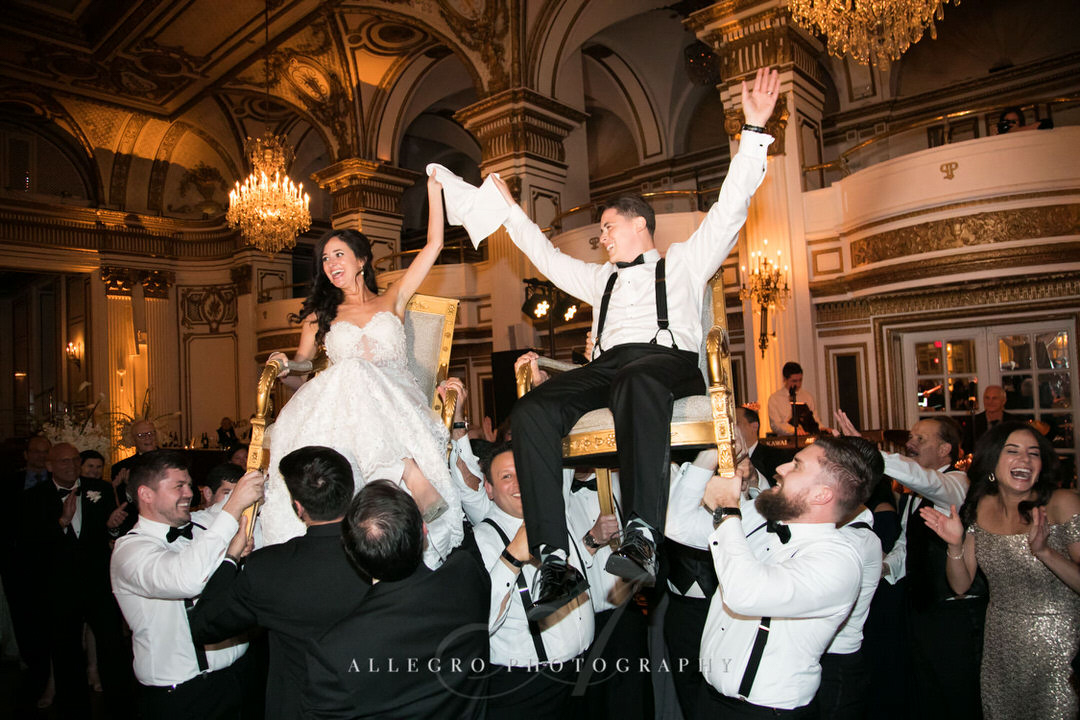 bride and groom get lifted for hora