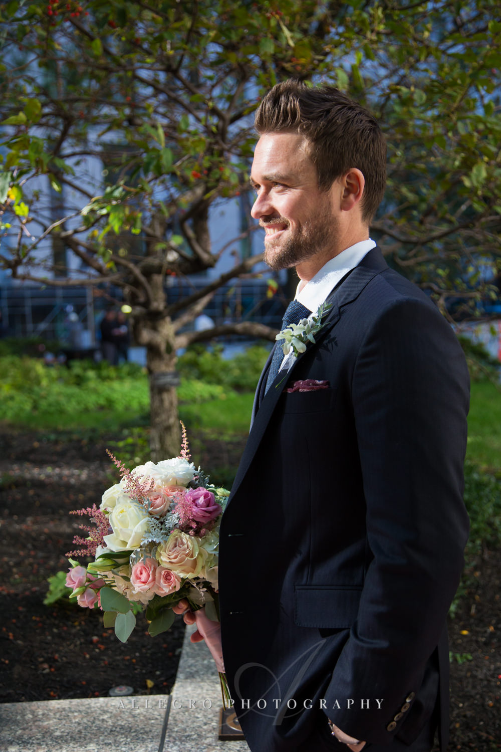 groom holds bouquet for bride