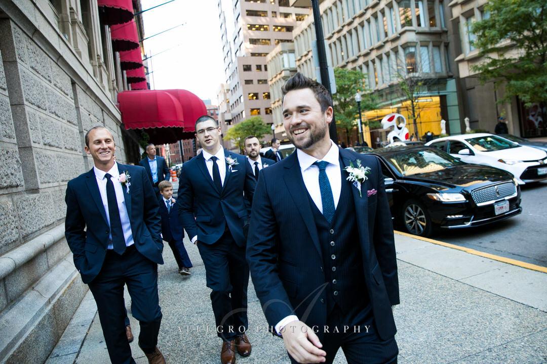 Smiling groom walking with his groomsmen