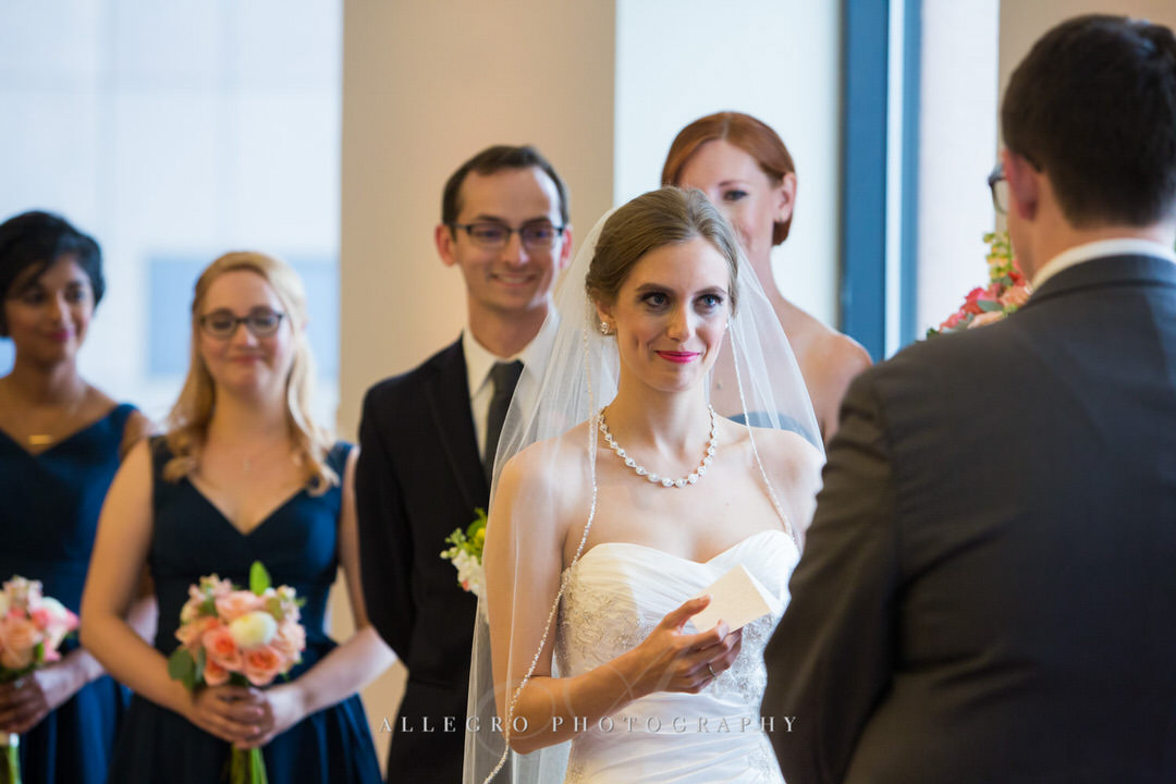 bride smiles as she reads wedding vows