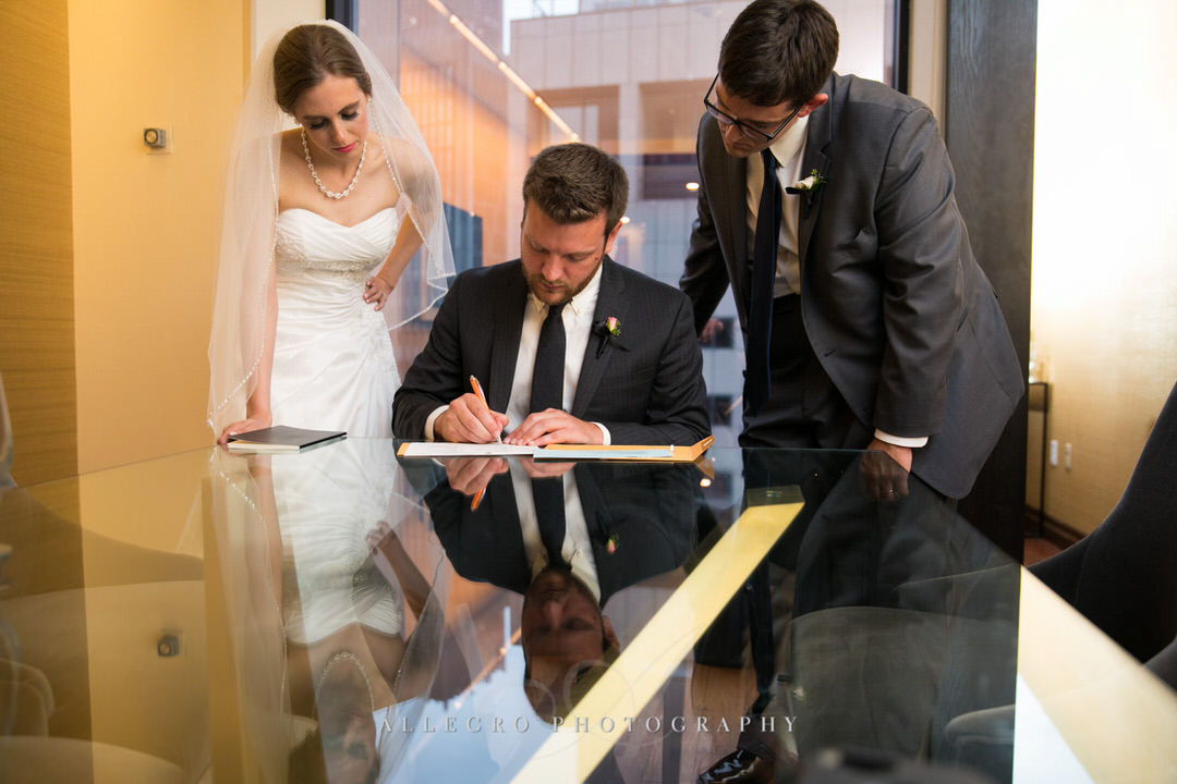 bride and groom watch as the wedding document gets signed