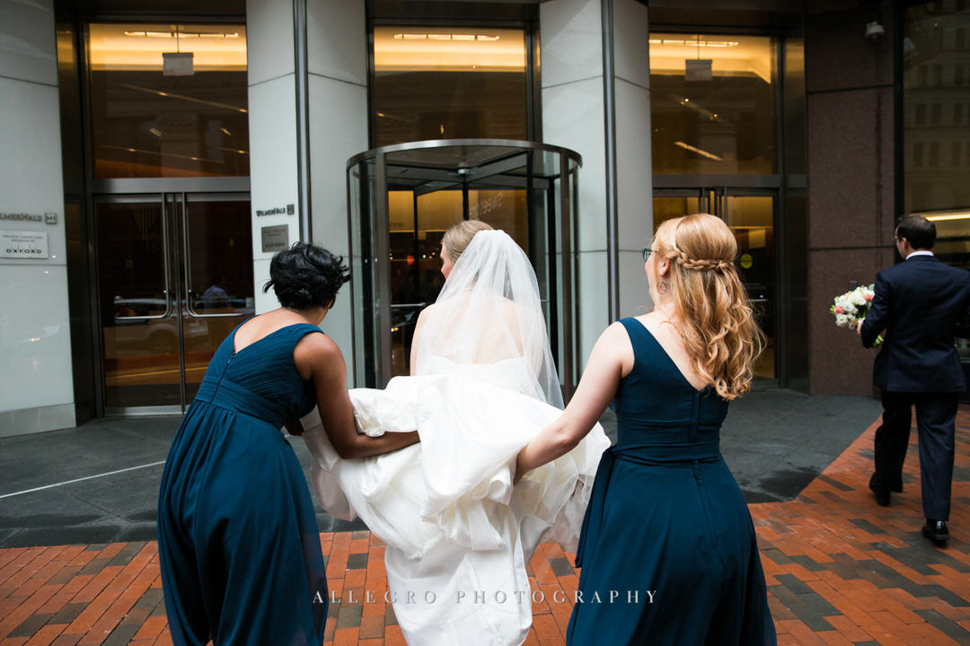 bridesmaids help bride with dress train