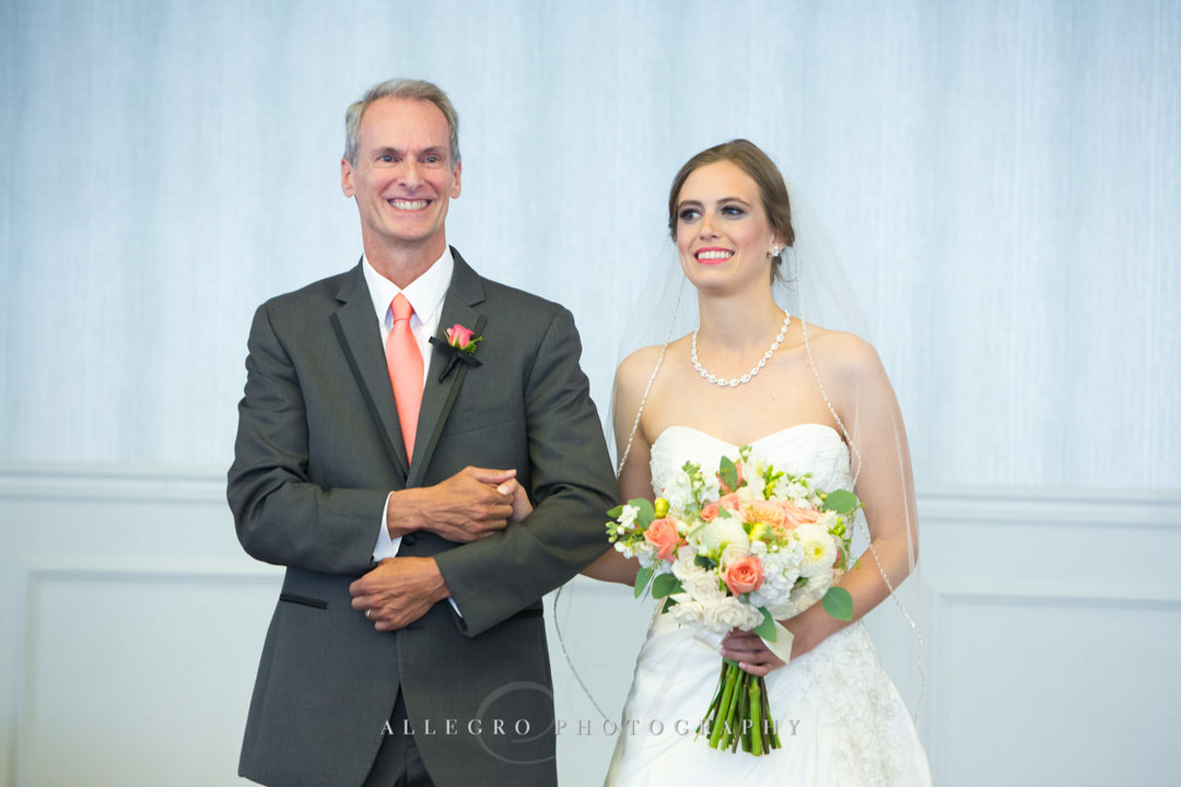 father of the bride smiles as he walks her down the aisle