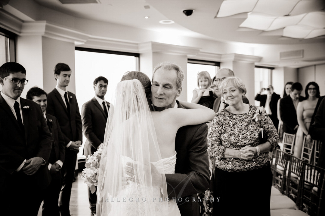 father of the bride hugs her after walking her down the aisle