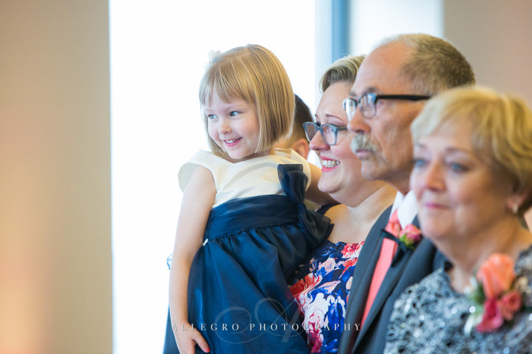 flower girl smiles while mom holds her