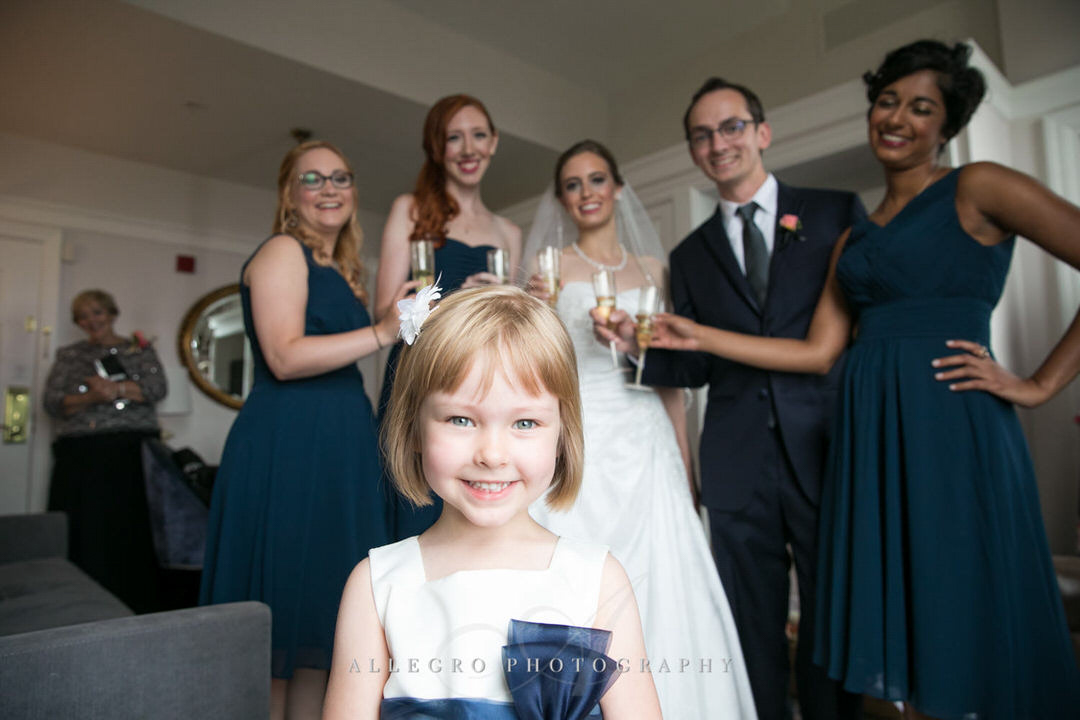 flower girl smiles with bride and bridesmaid in background