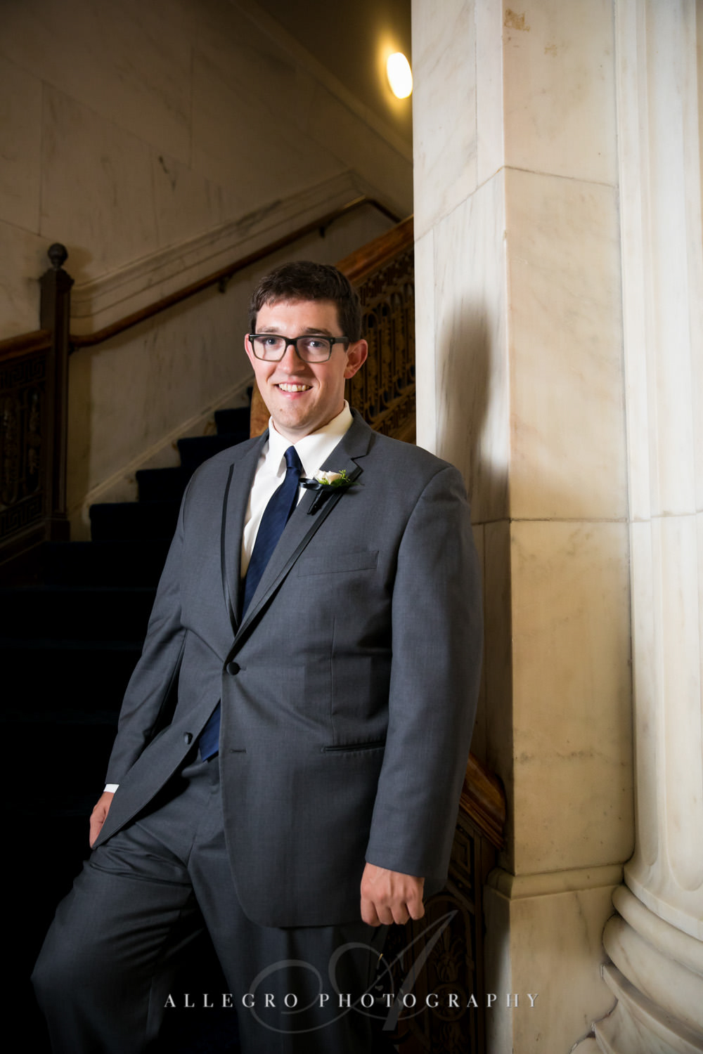groom poses on stairs in custom house