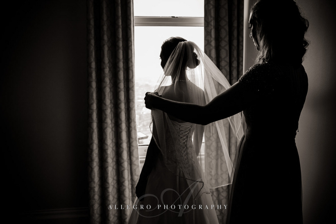 mother of the bride helps bride put on veil