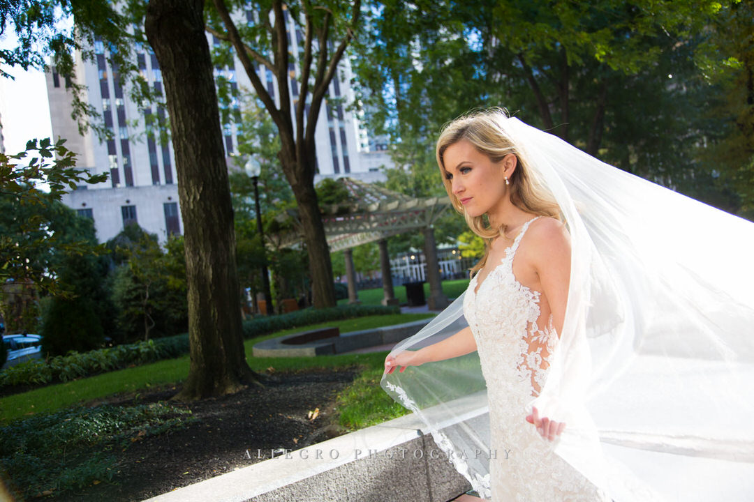 bride with veil blowing in the wind in post office park