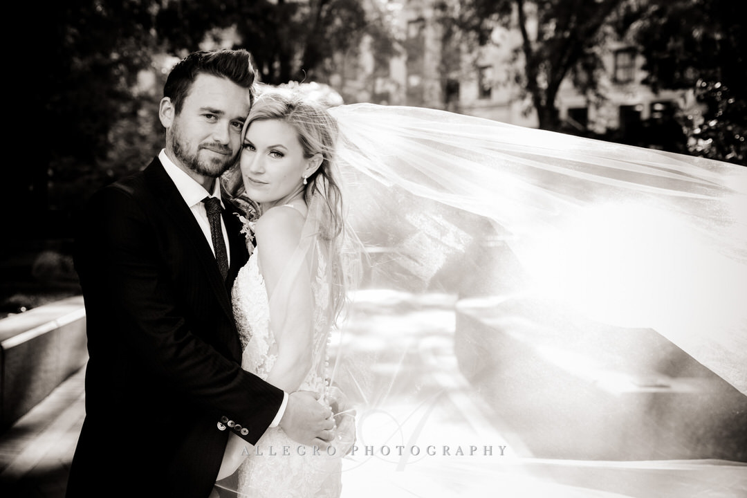 bride and groom in black and white with veil blowing in the wind
