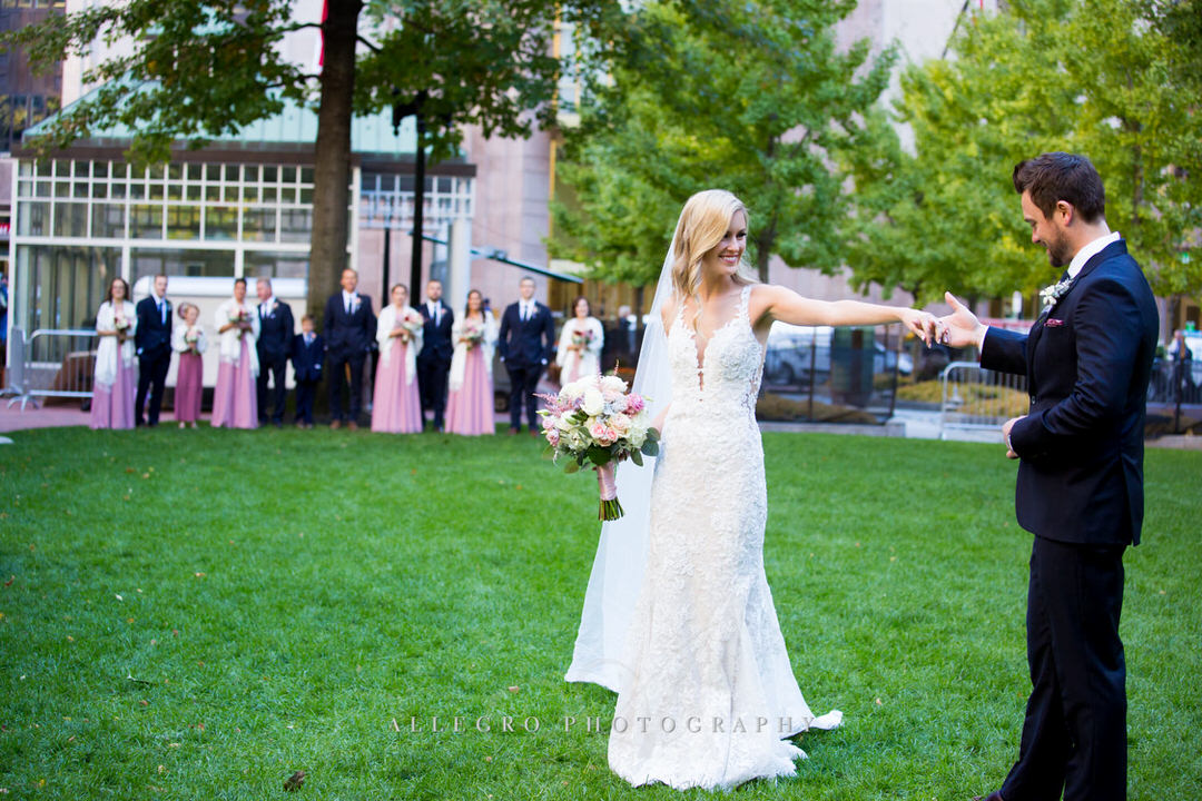 bride and groom dance in post office square while bridesmaids and groomsmen watch