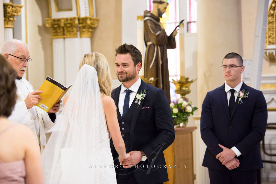 groom looks into brides eyes while at the altar