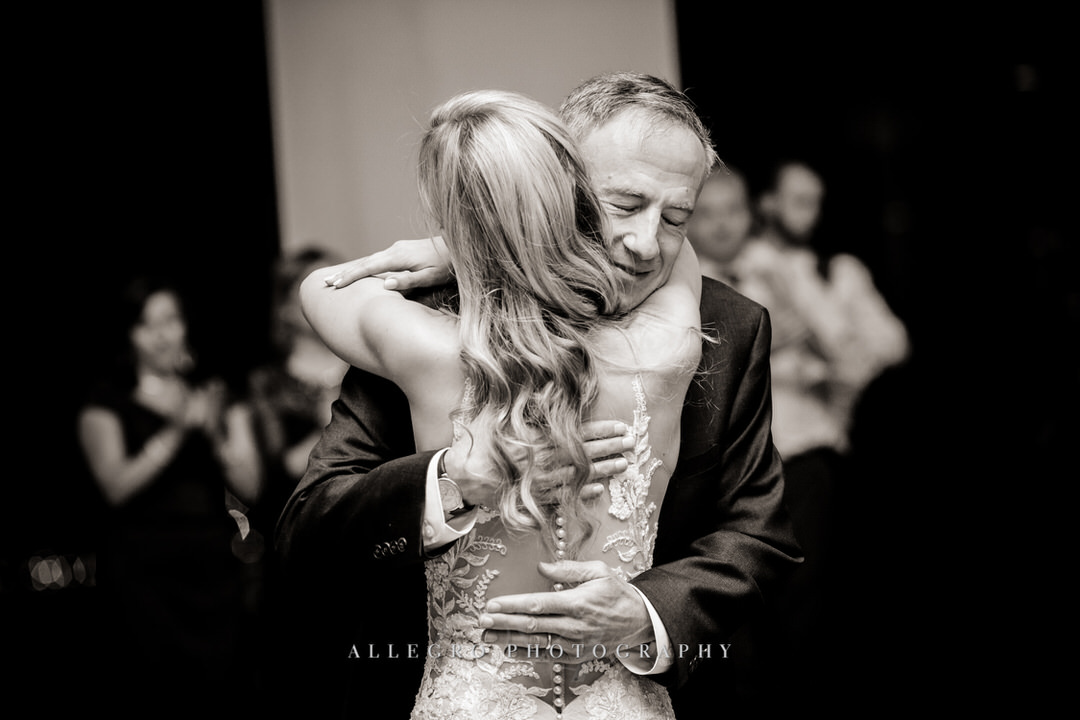 bride hugs father of the bride in black and white