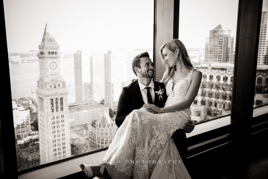 bride sits on grooms lap while smiling at each other in black and white